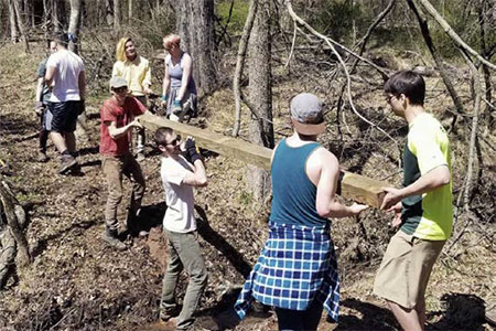 Members of TWS Rutgers Chapter haul wood down the trail for the new boardwalk.